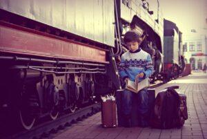Pojke med resväskor vid tåg på station