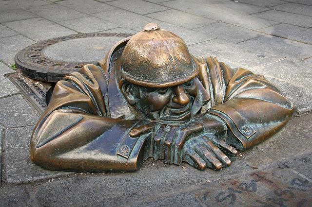 Staty som föreställer en man som kommer upp ur gatan.