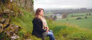 kvinna som sitter på en klippa
