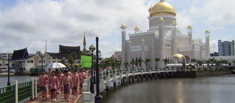 män som går över en bro med ett kupolförsett palats i bakgrunden
