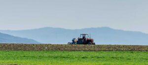 traktor på ett grönt fält med berg i bakgrunden