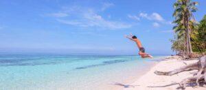 person som hoppar på en strand