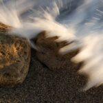 stenpå en strand som sköljs av vatten från havet