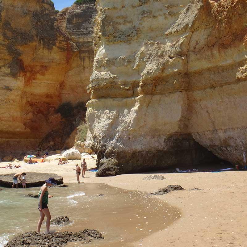 människor på en badstrand vid en klippa