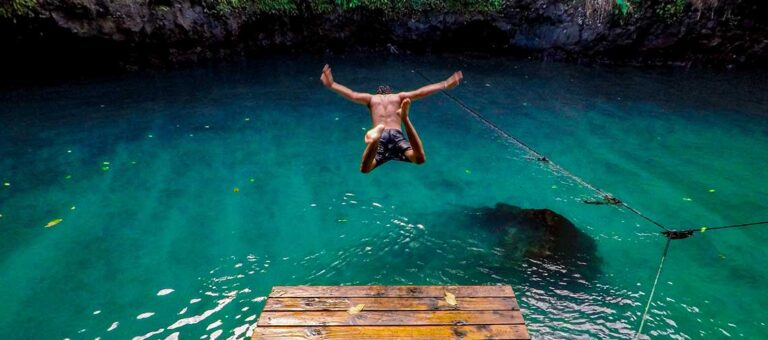 man som hoppar ner i vattnet från en brygga vid en klippa