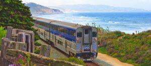 поезд на фоне моря и гор