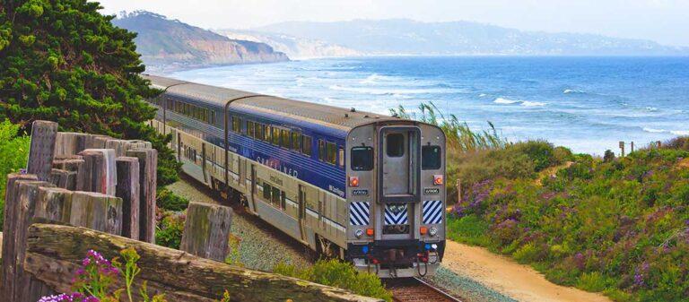tåg på räls med hav och berg i bakgrunden