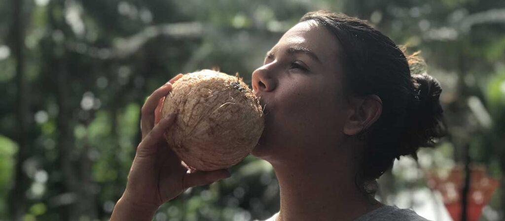 kvinna som dricker ur en kokosnöt