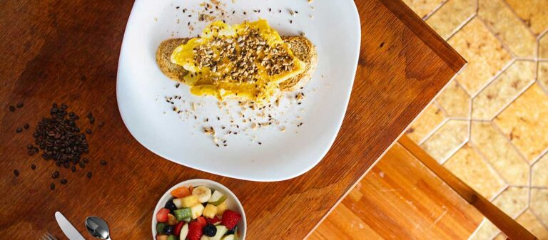 vita tallrikar med smörgås och fruktsallad