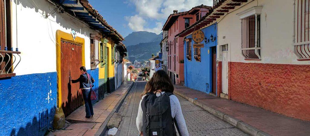 человек с рюкзаком идет по улице между домами