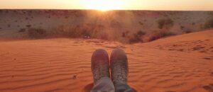 person som sitter på sanden