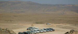 kamel och bilar på en parkeringsplats i öknen