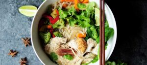 bruna ätpinnar på vit skål med grönsaker och nudlar