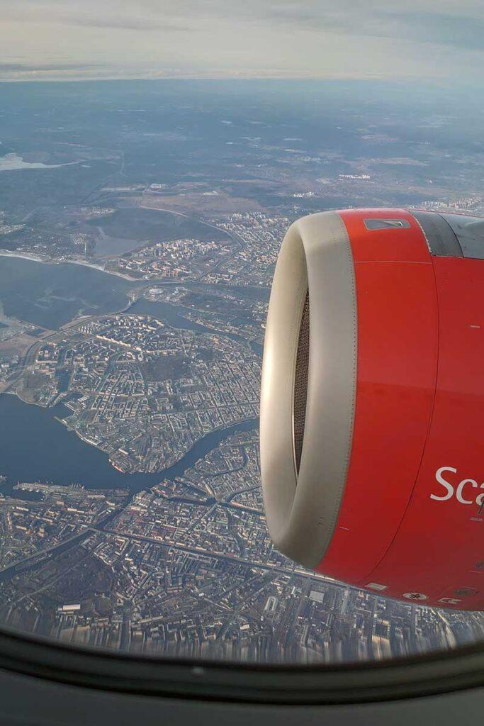 flygplansmotor sedd inifrån ett flygplan ovanför stad