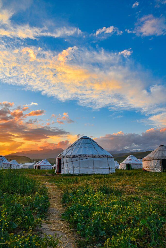 vita jurtor på gräsklädd mark under blå himmel