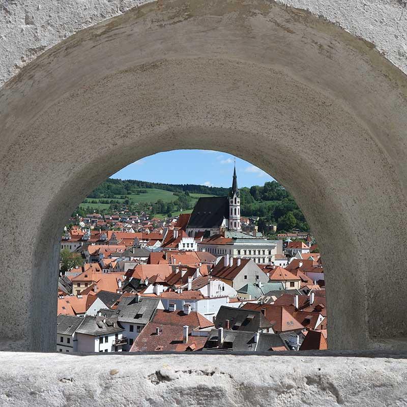 utsikt över gammal stad genom en glugg i en mur