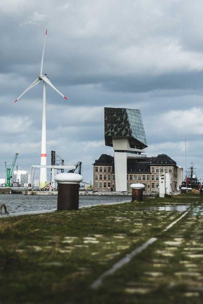 hamnkaj med vindkraftverk och kontorsbyggnad i bakgrunden