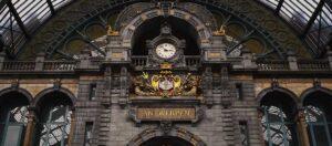 klocka och ortnamn på väggen inne på tågstation