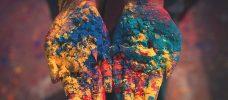 Händer fulla av färgpulver i olika kulörer.