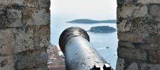 gammal kanon som står riktad från ett fort ut över havet