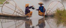 två personer som dricker te i varsin båt på en flod