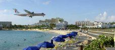 Flygplan på väg ner för landning över en strand