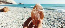sten i handen, strand i bakgrunden